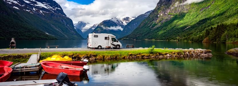 family trip in RV next to mountains and lake.